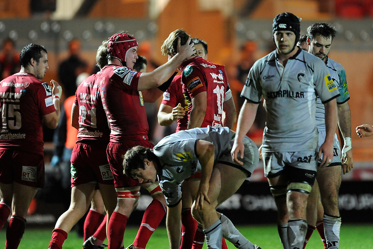 Johnathan Edwards (left) congratulates try scorer Phil John of Scarlets during the LV= Cup first round match between Scarlets and Leicester Tigers at Parc y Scarlets (Photo by Rob Munro, Fotosports International)