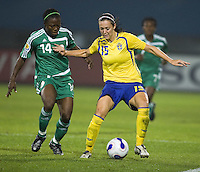 Sweden midfielder (15) Therese Sjogran tries to keep her distance from Nigeria defender (14) Faith Ikidi. Sweden (SWE) tied Nigeria (NGA) 1-1 during a FIFA Women's World Cup China 2007 opening round Group B match at Chengdu Sports Center Stadium, Chengdu, China, on September 11, 2007.