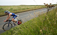 27 JUL 2013 - CROMER, GBR - Stephen Whitington makes his way along the coast road past the salt marshes at Salthouse, North Norfolk, Great Britain during The Anglian Triathlon (PHOTO COPYRIGHT © 2013 NIGEL FARROW, ALL RIGHTS RESERVED)
