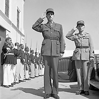 Tunisia. General de Gaulle, accompanied by General Mast, saluting as the band plays Marseillaise outside the summer palace of the bey of Tunis. in 1943<br /> exact date unknown