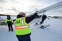 """An FAA inspector does a """"ramp check"""" on Iditarod Air Force pilot Daniel Hayde's plane at the Willow, Alaska airport during the Food Flyout on Saturday, February 20, 2016.  Iditarod 2016"""