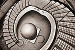 Black and white abstract of circular staircase culminating in a round ball