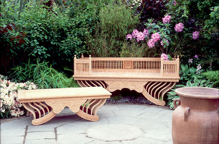 Beautiful wooden garden benches on patio in landscape