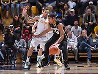 California's Justin Cobbs defending Colorado's Josh Scott during a game at Haas Pavilion in Berkeley, California on March 8th, 2014. California defeated Colorado 66 - 65