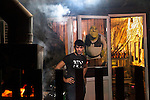 A shashlik (kebab) maker in the outskirts of Grozny, outside of a restaurant where he works, which has been decorated with poster of Shrek. Grozny, Chechnya, Russia, 2012
