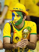 Dejected Brazil fan holds onto a world cup