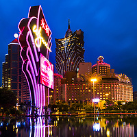 Twilight on the lit-up Grand Lisboa casino, with the Wynn casino neon sign in the foreground and light reflections on the hotel pond, in Macao, China