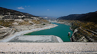 The water level in Kourris dam, when full, is marked by the dark vegetation high on the hills. Now it?s nearly empty like the other 55 damns in Cyprus. Agriculture doesn?t get any water from the reservoirs, boreholes are used to water the plants and livestock.