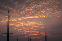 Buttermilk clouds with sunset glow punctuated by sailboat masts.