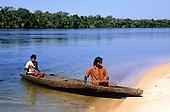Mato Grosso, Brazil. Rikbaktsa (Canoeiro) Indians arriving at a riverside beach in a dugout canoe.