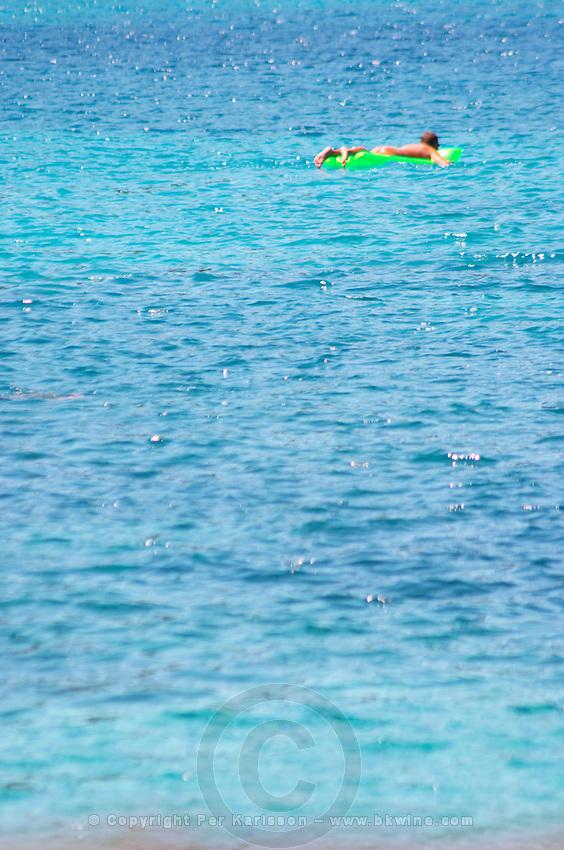 A man floating on inflatable air green mattress on a deep blue sea. Uvala Sumartin bay between Babin Kuk and Lapad peninsulas. Dubrovnik, new city. Dalmatian Coast, Croatia, Europe.