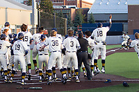 Michigan Wolverines bench celebrates a walk-off victory against the Michigan State Spartans during Big Ten NCAA baseball action at Ray Fisher Stadium on March 21st, 2021 in Ann Arbor, Michigan. Michigan scored 8 runs in the bottom of the ninth inning to win 8-7. (Andrew Woolley/Four Seam Images)