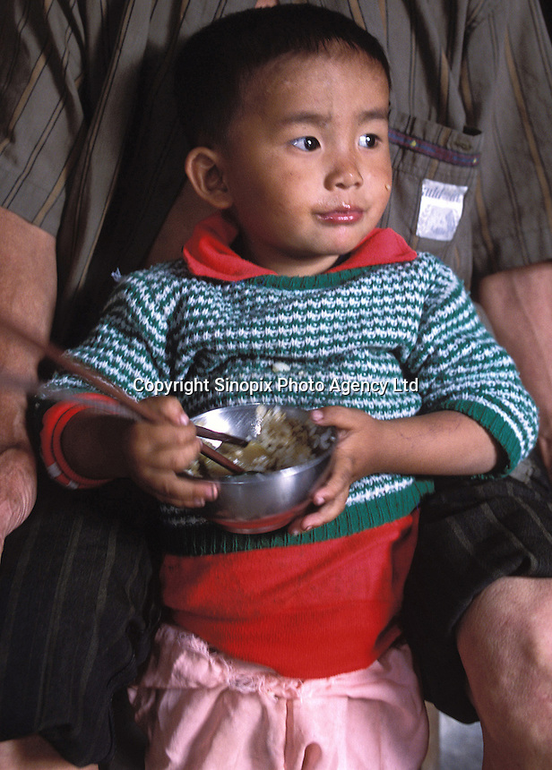 Qi Qi, a 3-year old boy eats rice and fish. The child and his five year old sister are kept in a cage in a village house belonging to their uncle. The children's parents are both in prison and the uncle is too poor to afford child care for the children and are afraid they may be stolen a common problem in China...PHOTO BY SINOPIX