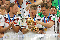 Miroslav Klose and Bastian Schweinsteiger of Germany look at the World Cup trophy after winning the 2014 final