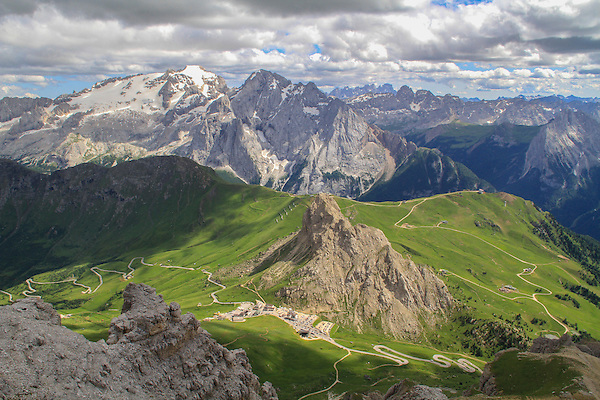 Italy, Dolomites. Ride to the Top.<br /> Photographers instinctively climb to high points to get the shot. The Alps have many more ski lifts than North American ski area, plus they're open in the summer. The pistes of Belvedere Ski Area spread across the green slopes far below. <br /> Atop the Sella Groupa Tram, with Passo Pordoi and Mt Marmolada in view, Italy.