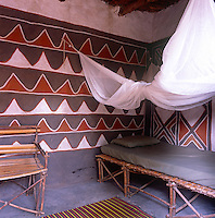 The interior of a traditional Dogon house in Mali with decorative paint effect on the walls and a rudimentary bed with a mosquito net.