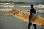 a palestinian surfer with his surfboard on the beach of gaza city on december 23,2014. Photo by Osama Baba