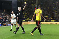 (L-R) Referee Martin Atkinson shows Marvin Zeegelaar of Watford a yellow card during the Premier League match between Watford and Swansea City at the Vicarage Road, Watford, England, UK. Saturday 30 December 2017