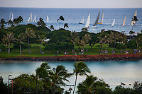 Sailboats return from Friday races beyond Magic Island, with Ala Moana Beach Park lap pool in the foreground, Honolulu, O'ahu.