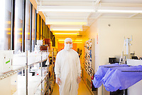 Aeronautics and Astronautics Ph.D. candidate Louis Perna is seen here in the clean room of the Technology Research Laboratory in the Microsystems Technology Laboratory at MIT in Cambridge, Massachusetts, USA. Researchers in the cleanroom have to wear a bunny suit or clean room suit while working to prevent contamination. Perna works on silicon MEMS fabrication and packaging in the ion Electrospray Propulsion System (iEPS) for CubeSats project at MIT. The iEPS device is used to maneuver a 10cm cubic satellite in space. Two Ph.D. candidates working on the project, Natalya Brikner and Louis Perna have formed a company, Accion Systems Incorporated, to commercialize the research. Brikner, graduating in Winter 2014, is CEO of the company, and Perna is co-founder.