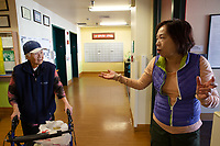 SEATTLE, WA - MARCH 20: Teresa Moy (R) drops off face cream and pears for her mother at the International Community Health Services' assisted living facilty, the Legacy House, on March 20, 2020 in Seattle, Washington. The International Community Health Services is a non-profit clinic that cares for uninsured patients, low income people and immigrants who rely on federal aid programs. Non-profit community health centers around the country are facing the expiration of federal funding they rely on in May as coronavirus (COVID-19) continues to spread. (Photo by Karen Ducey/Getty Images)