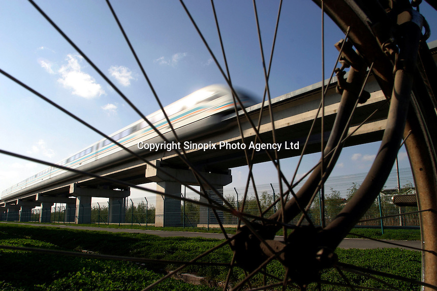 A Shanghai Transrapid magnetic levitation train speeds past a parked bicycle in Shanghai, China. ©Qilai Shen/Sinopix