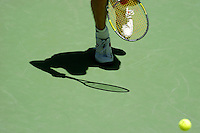 A shadow of a man running for the tennis ball on the court.