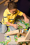 Education Preschool 4-5 year olds  boy playing with small toy cars and ramp he made from wooden blocks  vertical