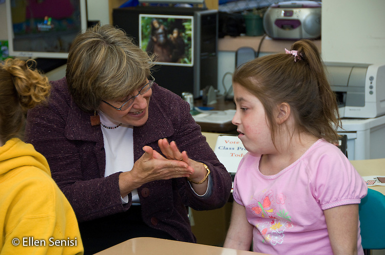 MR / Albany, NY.Langan School at Center for Disability Services .Ungraded private school which serves individuals with multiple disabilities.Teacher of Deaf and Hard of Hearing uses sign language to communicate with student (girl, 11, cerebral palsy, non verbal with expressive and receptive language delays) about what is happening in the classroom during speech and language development lesson..MR: Mor15, Gor3.© Ellen B. Senisi
