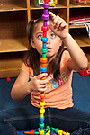 Education preschool 3-4 year olds girl counting pegs in tower she made