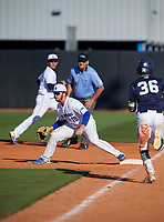 IMG Academy Ascenders Jack Fortin (19) stretches for a throw as Armando Guirola (36) runs up the base line during a game against the Victory Charter School Knights on February 28, 2020 at IMG Academy in Bradenton, Florida.  (Mike Janes/Four Seam Images)