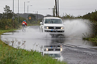 A cyclist attempts to negotiate riding through a flooded part of Water Street, while a car is seen driving in the opposite direction between the areas of Port Talbot and Pyle in south Wales, UK. Sunday 29 September 2019