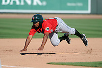 Fort Wayne TinCaps second baseman Reynaldo Bruguera (9) slides head first into third during a game against the Great Lakes Loons on August 18, 2013 at Dow Diamond in Midland, Michigan.  Fort Wayne defeated Great Lakes 4-3.  (Mike Janes/Four Seam Images)