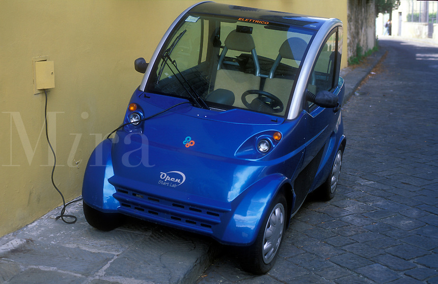 Italy, Florence, Tuscany, Electric car being charging at wall outlet