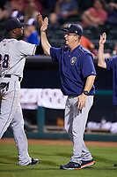 Colorado Springs Sky Sox coach Al LeBoeuf (10) high fives center fielder Lewis Brinson (28) after a game against the Oklahoma City Dodgers on June 2, 2017 at Chickasaw Bricktown Ballpark in Oklahoma City, Oklahoma.  Colorado Springs defeated Oklahoma City 1-0 in ten innings.  (Mike Janes/Four Seam Images)