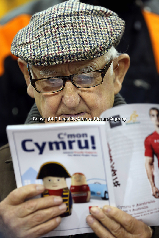 Pictured: An elderly Wales supporter reading the match programme. Saturday 08 November 2014<br /> Re: Dove Men Series rugby, Wales v Australia at the Millennium Stadium, Cardiff, south Wales, UK.