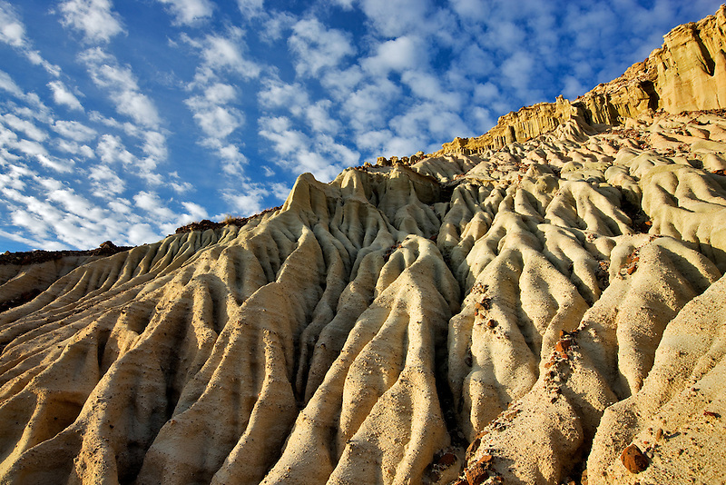 Eroded cliff with puffy clouds. Red Rock Canyon State Park, California