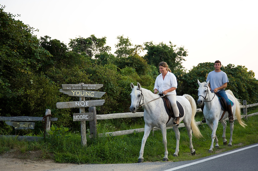 A couple rides horses along a road in Chilmark on Martha's Vineyard.....