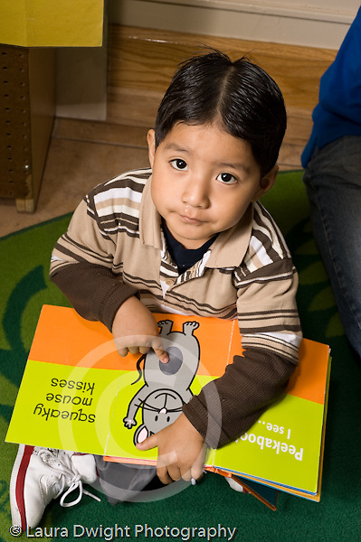 Education preschoool children ages 3-5 boy looking up at camera as he demonstrates pushing on page to make a squeaking sound vertical