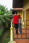 Vietnamese  young male and young female stand outside of room at hotel on balcony looking at garden with palm trees and plants