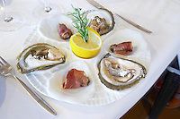 Oysters in two fashions: fresh and rolled in bacon with a lemon and rosemary on a white plate on a set dining table from the luxury Excelsior Hotel and Spa restaurant terrace Dubrovnik, old city. Dalmatian Coast, Croatia, Europe.