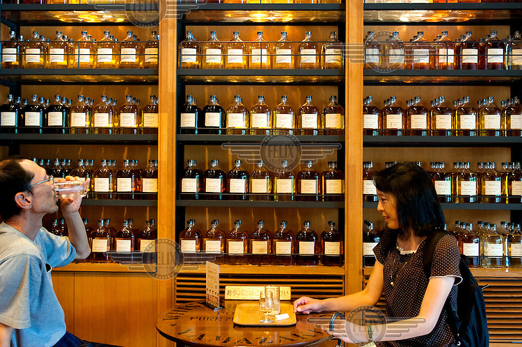 Visitors on the Yamazaki Distillery tour try a sample at the tasting counter. On offer are about 100 varieties of whisky. The company, founded in 1899, it produced its first whiskey in 1929.