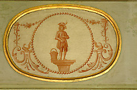 A gilt-framed hand-painted oval panel depicting a shoeless beggar standing next to a basket of fruit