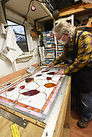"""THROUGH THE LOOKING GLASS<br />Dennis """"Hete"""" Heter, stained glass artist, puts the finishing touches Wednesday Jan. 6 2020 on a stained-glass window at his studio in east Benton County. The window is for a customer in Oregon and features red leaves with stems. Heter works full time at his craft and sells his stained glass acros the country. Go to nwaonline.com/210107Daily/ to see more photos.<br />(NWA Democrat-Gazette/Flip Putthoff)"""