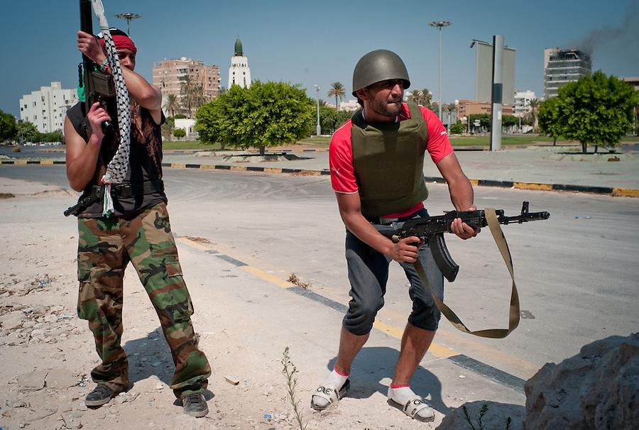 Rebel fighters engage Gaddafi soldiers near the Bab Al Aziziya compound in Tripoli, Libya