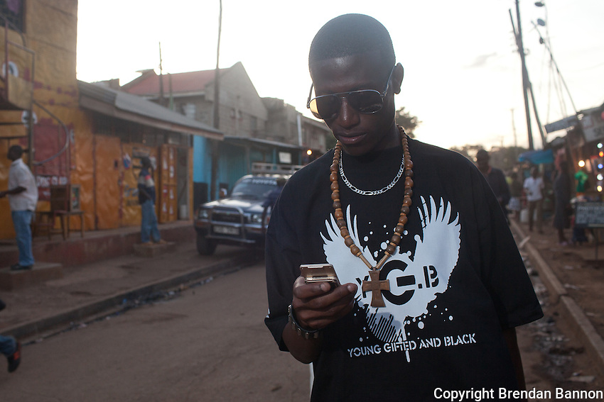 23-year-old hip-hop artist Octopizzo checking email on his mobile phone in Kibera.