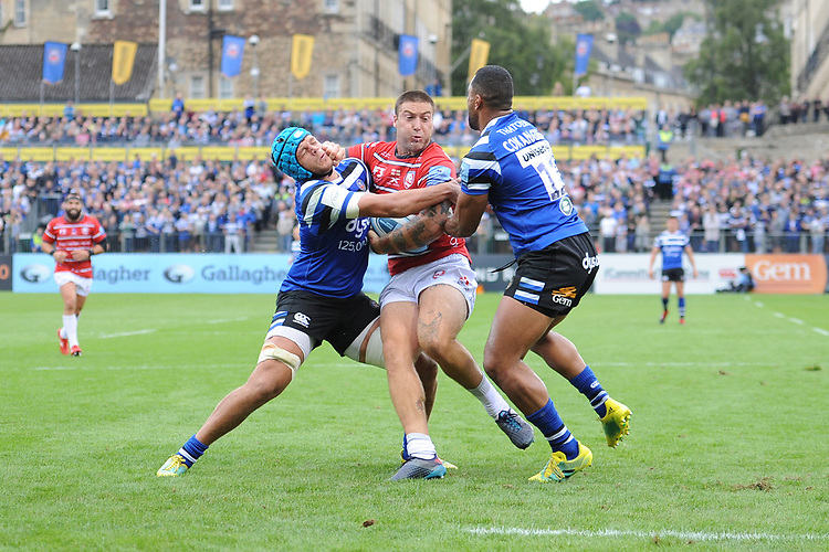 Matt Banahan of Gloucester Rugby is stopped short of the line by Zach Mercer and Joe Cokanasiga of Bath Rugby during the Gallagher Premiership Rugby match between Bath Rugby and Gloucester Rugby at The Recreation Ground on Saturday 8th September 2018 (Photo by Rob Munro/Stewart Communications)