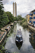 Trellick Tower and houseboats on the Paddington branch of the Grand Union canal. The number of people living on London canals has risen sharply as a result of rising rents and property prices in the capital.