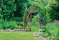 Garden arch or arbor with blooming clematis in blue and red on summer afternoon, Missouri USA