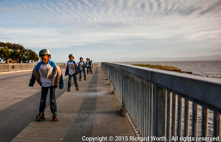 Five sequential images, merged into one, of a boy roller skating across a bridge at the San Leandro Marina Park.